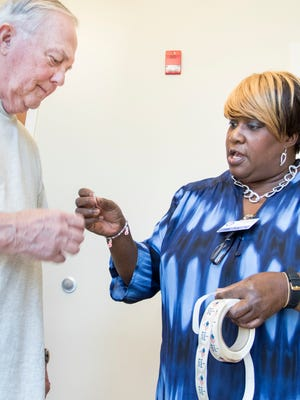 """Poll worker Sandra Savage hands an """"I Voted Early"""" sticker to Frank Hall after he voted at the libary on Spring Street in Pensacola on Monday, October 24, 2016.  Early voting is from October 24 through November 5."""