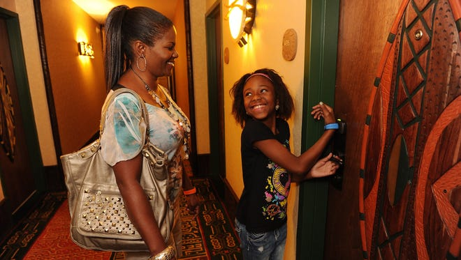 Disney hotel guests Faithlyn Martin and Shekinah Martin use MagicBand+ technology to enter their room.
