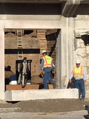 Work crew finished cutting through concrete wall, creating