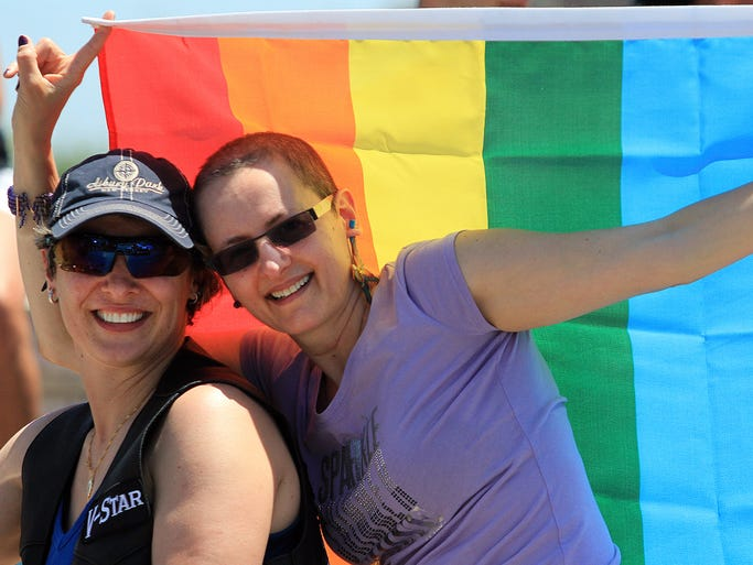 ASB 0602 GAY PRIDE Isabelle Ferreira, of Asbury Park, left, and partner Fabiula Silva, who were married in Nov. 2013, show their pride during the Jersey Pride parade and festival in Asbury Park, Sunday, June 1, 2014. Asbury Park, NJ - Photo by Mary Frank