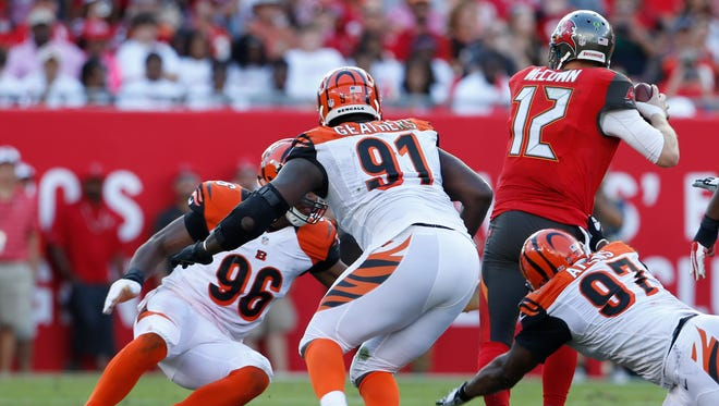 Tampa Bay Buccaneers quarterback Josh McCown (12) is sacked by Cincinnati Bengals defensive end Carlos Dunlap (96) as he is chased by defensive end Robert Geathers (91)and Cincinnati Bengals defensive tackle Geno Atkins (97) during the fourth quarter of their game played at Raymond James Stadium in Tampa, Florida Sunday November  30, 2014. The Enquirer/Gary Landers