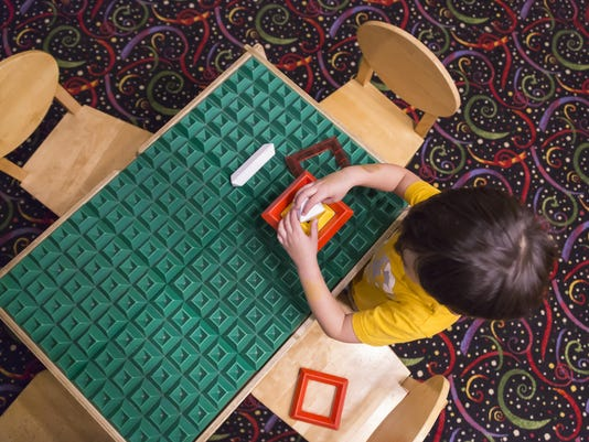 Overhead of Boy Playing With His Toys at Table