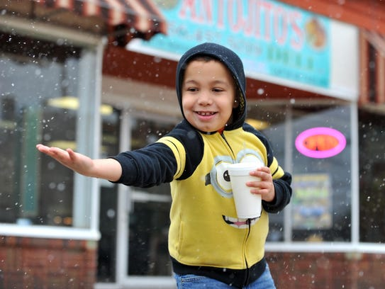 Julian Barrera, 8, catches snowflakes in his hand,