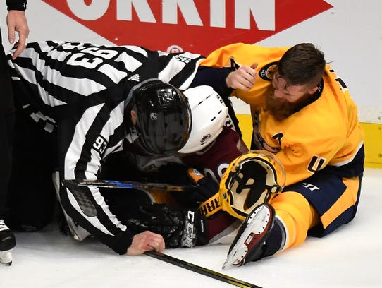 Linesman Brian Murphy tries to break up a fight between