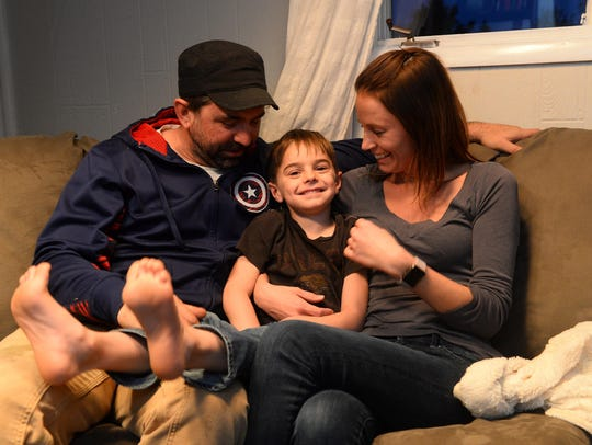 Henry Merrill, age 5, sits with his parents, Nathan