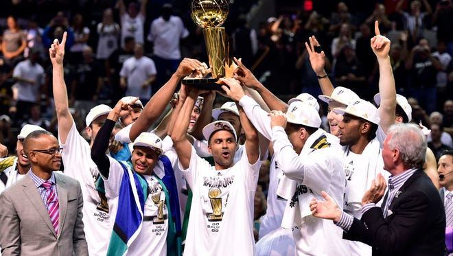 The San Antonio Spurs celebrate with the Larry O'Brien Trophy after game five of the 2014 NBA Finals against the Miami Heat at AT&T Center on June 15, 2014.