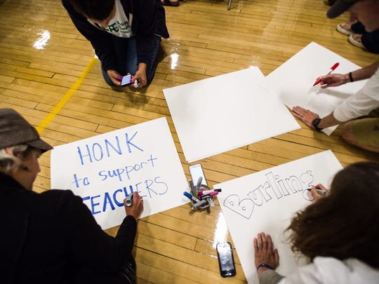 Teachers take to the floor to make posters after hearing that a planned 8 p.m. Burlington School Board meeting at Edmunds Middle School would be delayed several hours and the board and union continued to wrestle with contract negotiations Thursday night, Aug. 31, 2017.