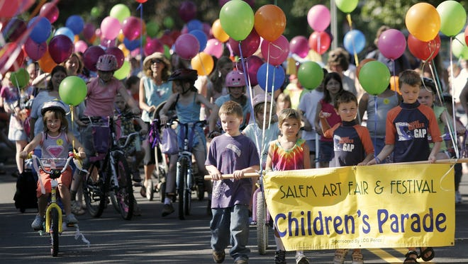 Children head down High Street SE as part of the Children's Parade at the beginning of the annual Salem Art Fair in Bush's Pasture Park