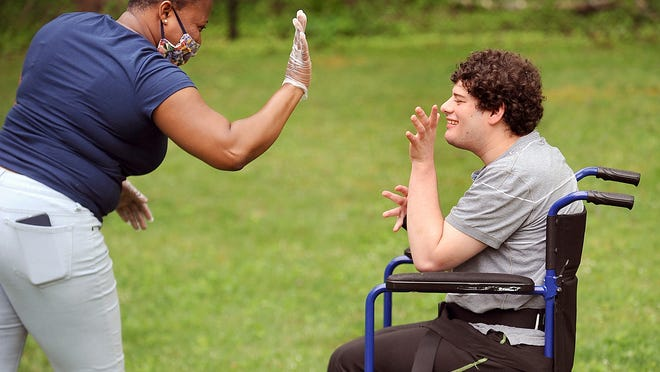 Wilhemina Opoku, a residential assistant at the Guild of Human Services Framingham house, works with resident Jason Rideman in the backyard.