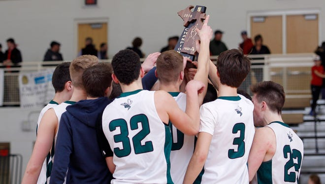 Williamston players celebrate with their Class B regional championship trophy after defeating Marshall, Wednesday, March 14, 2018, in Fowlerville, Mich. Williamston won 48-40.