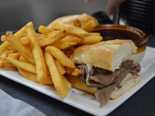 French dip with homemade Au Jus sauce and fries at