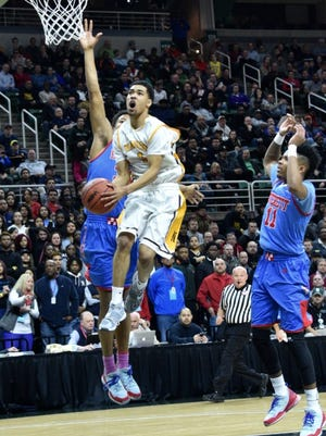 North Farmington's Billy Thomas drives to the basket in the first half. North Farmington defeated Lansing Everett 60-48 Friday in the Class A semifinal at the Breslin Center.