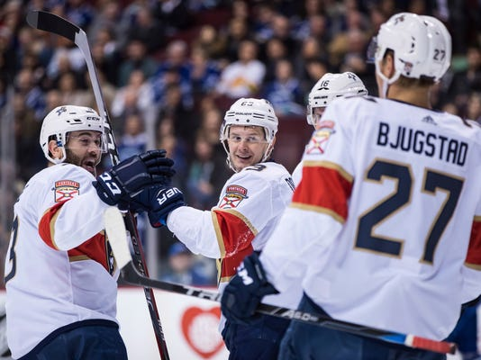 Florida Panthers' Keith Yandle; Evgenii Dadonov, of Russia; Aleksander Barkov, of Finland; and Nick Bjugstad celebrate Dadonov's goal against the Vancouver Canucks during the first period of an NHL hockey game Wednesday, Feb. 14, 2018, in Vancouver, British Columbia. (Darryl Dyck/The Canadian Press via AP)
