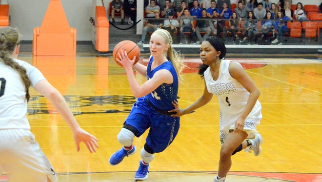 Carlsbad's Carsyn Boswell attacks the lane against Hobbs' Amiah Smith (4) and Payton O'Brain (10) in Saturday's district championship tiebreaker game at Artesia. The Cavegirls look to start fresh after losing back-to-back games to the Lady Eagles Friday and Saturday.