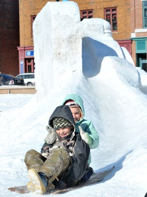 In this file photo, Carter Bayer, front, and his sister Vanessa, both of Merrill, sled on a giant snow sled sculpture during Saturday's Winter Fest at The 400 Block in downtown Wausau, Feb. 11, 2012.