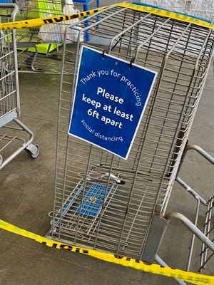 Shopping carts, caution tape and signs advising customers to practice social distancing are lined up at Walmart's entrance in Columbia. The new policy enacted Thursday requires customers to enter and leave the store in single-file.