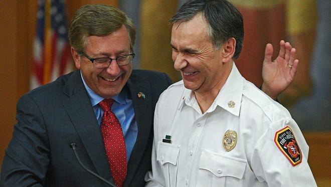 Sioux Falls Mayor Mike Huether pats Sioux Falls Fire Rescue Chief Jim Sideras, right, on the back at the end of a press conference announcing the retirement of Sideras at City Hall last month.