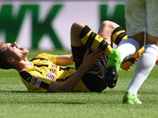 Dortmund's Julian Weigl is injured after a foul during the German Bundesliga soccer match between FC Augsburg and Borussia Dortmund at the WWK Arena in Augsburg, Germany, Saturday, May 13, 2017. (Andreas Gebert/dpa via AP)