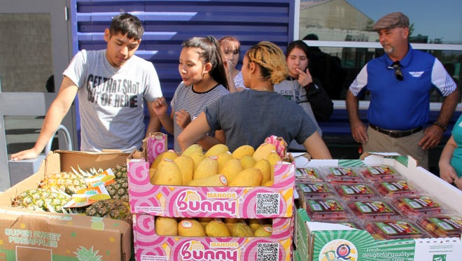 Principal Stan Lyons, far right, helps his Deming Cesar Chavez Charter High School students organize the school's first-ever mobile food pantry at Deming High School on April 23. The food was provided by Roadrunner Food Bank of New Mexico and served about 50 families of students at DHS.