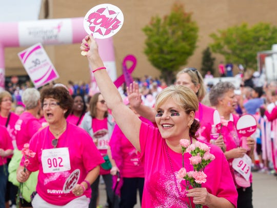 Twenty-eight years survivor Debbie Moody of Newburgh smiles and holds up her Pow! sign as she marches in the Parade of Pink before the start of Race for the Cure at Eastland Mall in 2105.