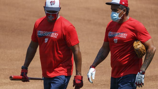 Nationals manager Dave Martinez, left, and bullpen coach Henry Blanco make their way around practice for the team on Sunday. They stayed home on Monday after the team called off workouts.