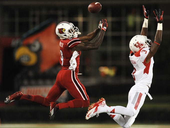 UofL's Devante Parker (8) battles Houston's Deontay Greenberry (3) for a pass on Saturday at Papa John's Cardinal Stadium but was an incompletion. Nov. 16, 2013