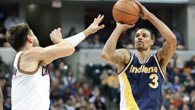Pacers guard George Hill fires a shot over Cleveland guard Matthew Dellavedova in the first half of the game at Bankers Life Fieldhouse on Friday, Feb. 27, 2015. Hill had his first career triple double and the Pacers defeated the Cavaliers 93-86.