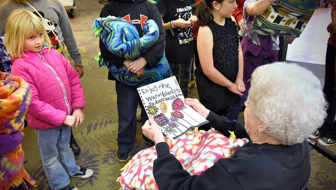 Children from the Clearview and Talahi KIDSTOP programs present warm blankets and handmade cards Thursday to St. Benedict's Senior Community residents. The children made the blankets and cards on the United Way's Day of Caring.