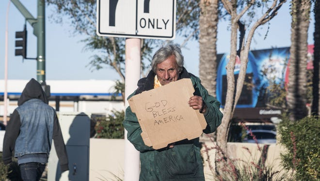 A homeless man begs on a Phoenix street in December 2015. Phoenix police and city social workers try to find homeless people to provide services if they qualify.