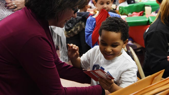 Baron Santana, right, 5, gives a hug to Veronica Schetter, left, assistant director of City of Beacon Housing Authority, after receiving a $25 gift card to Kohl's. The gift cards were funded by Holiday Helping Hand.