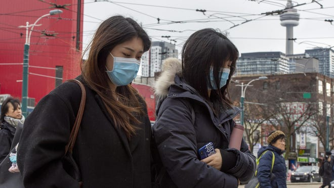 Pedestrians wear protective masks as they walk in Toronto on Monday. Canada's first presumptive case of the novel coronavirus has been officially confirmed, Ontario health officials said Monday as they announced the patient's wife has also contracted the illness.