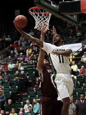 CSU senior forward Stanton Kidd (11) shoots a reverse layup along the baseline Saturday night against Montana senior center Chris Kemp (24) at Moby Arena. The Rams won their season opener 83-66.