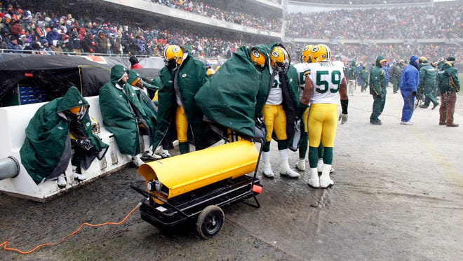 On a cold and blustery day in Chicago on Dec. 23, 2007, the Packers try to warm up on the bench during a 35-7 loss to the Bears.