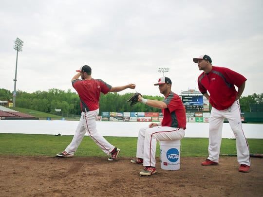 Zachary Lawhorn of Frostburg State University uses an imaginary bat as Connor Cooper catches a real ball and Greg Schneider makes the call as they wait out a weather delay Sunday, May 24, 2015, the third day of play at the NCAA Division lll Baseball Championship at Neuroscience Group Field at Fox Cities Stadium in Grand Chute, Wis.