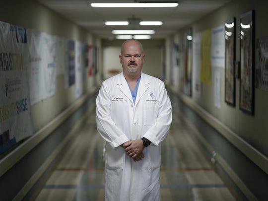 In this Wednesday, May 29, 2019 photo, Dr. Dave MacIntyre poses for a portrait at Sunrise Hospital in Las Vegas. He is part of a vast community of people touched by America's mass shootings. Traumatized after treating dozens of victims from a 2017 Las Vegas concert massacre, MacIntyre plans to leave surgery and help train others in coping with similar challenges. (AP Photo/John Locher)