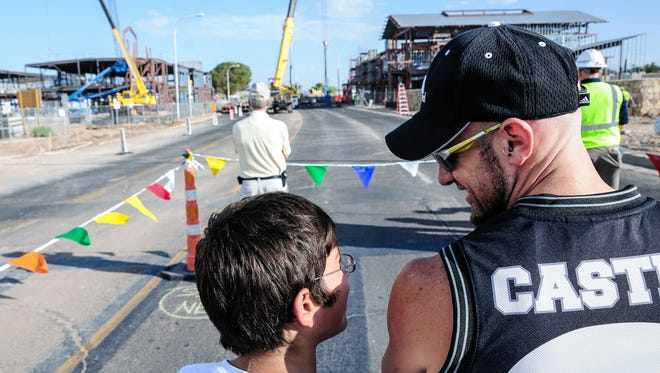 "Ken Lape, right, and his son Roman, 12, watch as the Las Cruces High School bridge is constructed. Lape is a construction worker on the project, but is off on Fridays, ""I didn't want to miss this,"" he said."