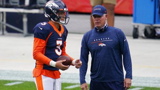 Denver Broncos quarterback Drew Lock, left, confers with offensive coordinator Pat Shurmur during an NFL football practice in empty Empower Field at Mile High on Saturday in Denver.