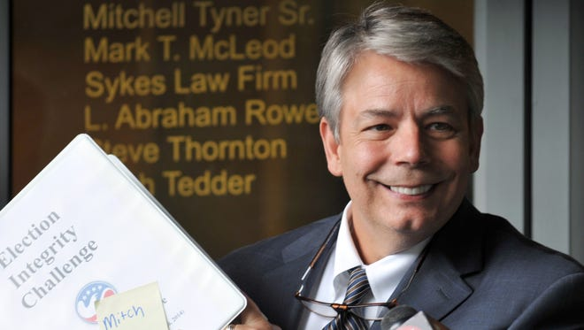 Attorney Mitch Tyner Sr. holds up documentation for senatorial candidate Chris McDaniel's election challenge during a press conference Monday at his office on I-55 N Frontage Road in Jackson.