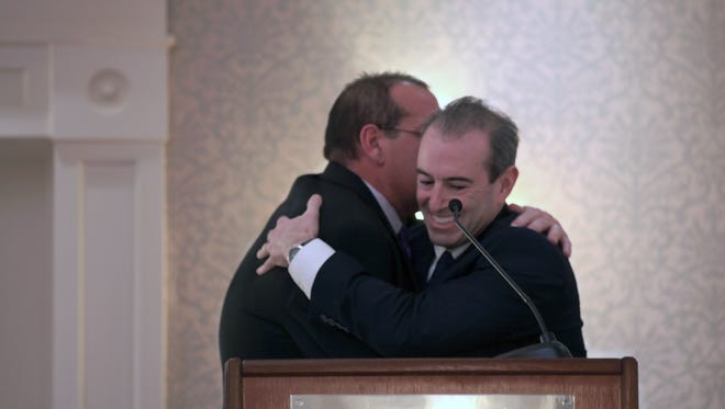 Cousins Peter Siracuse and David Penrose embrace in a hug after the co-owners received the 2016 Microenterprise of the Year award for Benefit Representatives of America, Inc.