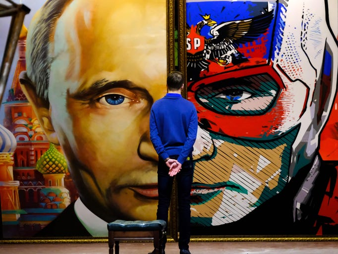 A man looks at a painting depicting Russian President