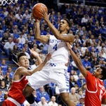 Kentucky's Charles Matthews (4) shoots between Boston University's Nick Havener, left, and Eric Johnson during the first half of an NCAA college basketball game Tuesday, Nov. 24, 2015, in Lexington, Ky.