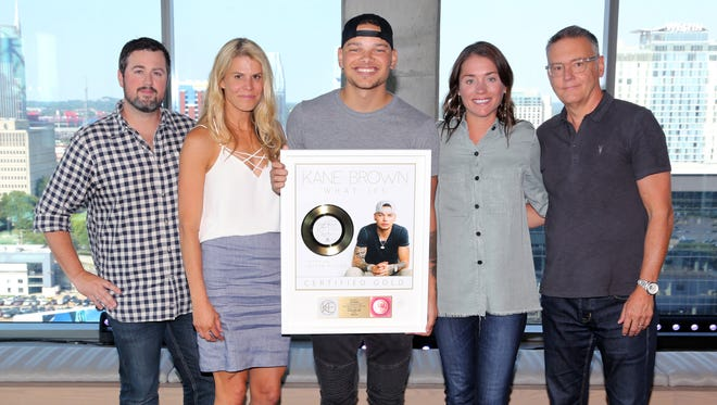 """At Kane Brown's surprise """"What Ifs"""" gold certification event are, from left, WME's Braeden Rountree; efg Mgmt's Martha Earls; Kane Brown; Liz Kennedy of the Recording Industry Association of America; and Sony Music Nashville Chairman and CEO Randy Goodman."""