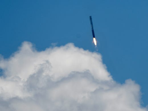 A SpaceX Falcon 9 rocket travels through the clouds