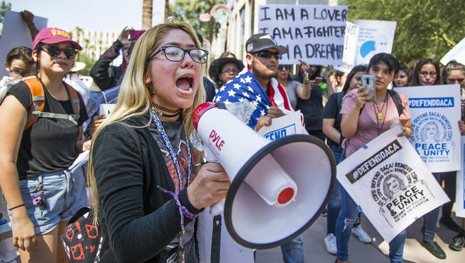Berania Yanez, 16, shouts from a megaphone to other students from North High School who are protesting the Trump administration's decision to phase out the Deferred Action for Childhood Arrivals program outside the Phoenix ICE offices on Sept. 5, 2017.