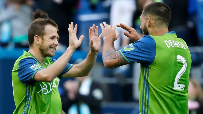 Sounders midfielder Harry Shipp (left) is greeted by forward Clint Dempsey after Shipp scored against the New York Red Bulls in Seattle's home opener.