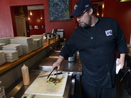 Chef Ryan Tracy prepares a crab cake BLT sandwich at