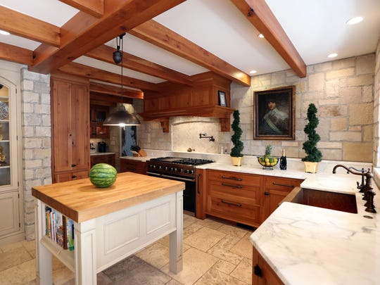 The home features a custom kitchen with knotty Cherrywood, natural stone walls and marble countertops.