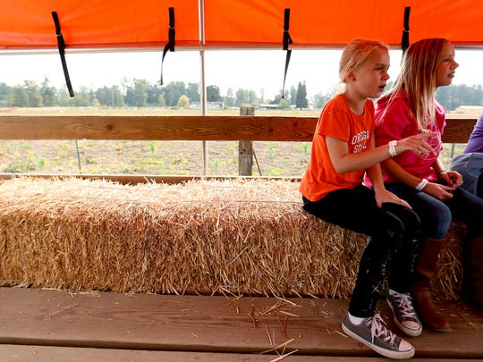 Friends Kaylee Cordle, 7, left, and Sam Rubesh, 11, of Albany ride on the tractor trailer to the pumpkin patch at Greens Bridge Gardens in Jefferson.