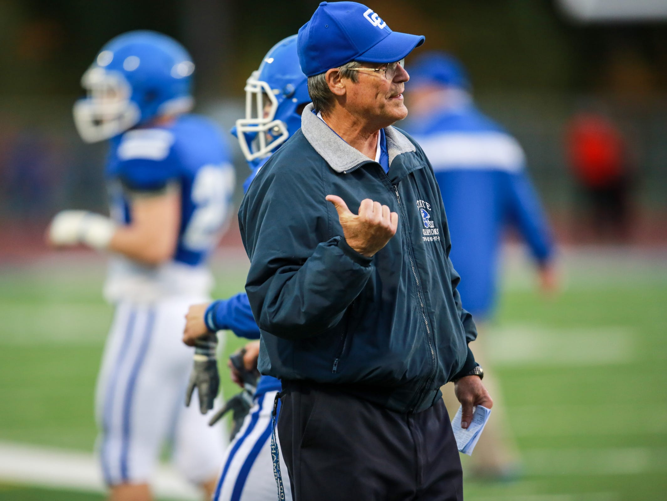 Novi Detroit Catholic Central Head Coach Tom Mach talks to other coaches before the start of the football game against Orchard Lake St. Mary's at Catholic Central in Novi, Mich. on Friday, Oct. 9, 2015.