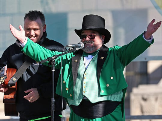 Leprechaun Michael McCracken, right, thanks the crowd with performer Eunan McIntyre, of County Donegal, Ireland, during the 36th annual St. Patrick's Day celebration, Thursday, March 17, 2016, Indianapolis, Ind.
